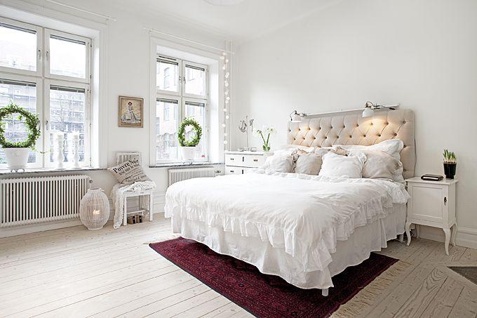 Jasna, niemal zupełnie biała sypialnia z wielkim łożem z pikowanym wezgłowiem.Mocniejsze kolory wprowadzają tu bordowy...