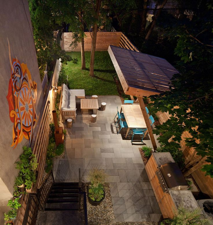 This backyard has an outdoor kitchen and covered dining area, as well as a lounge and fireplace.