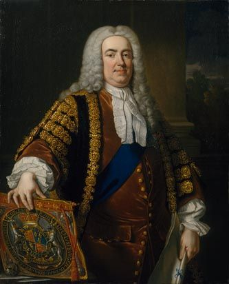 Robert Walpole is pictured here, the man considered first Prime Minister.    He is shown wearing the black and gold robes of the Chancellor and garter ribbon and star, indicating his membership of the Order of the Bath.