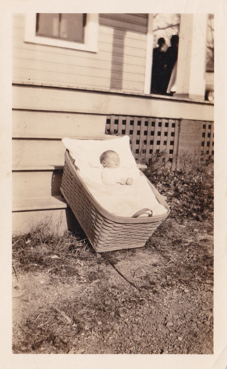 S/he is laid out in a basket, leaning against porch stairs. Guests are seen on the porch in the background.