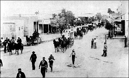 Allen street, Tombstone, looking east, with a parade in progress.  Main entrance to O. K. Corral in clump of trees, top center.  Photo courtesy the author, W. B. Shillingberg.