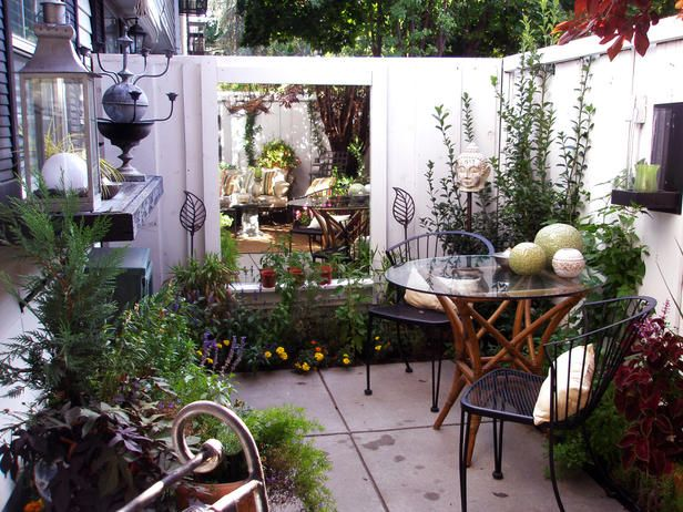 Small courtyard patio makes good use of large outdoor mirror, small table set and perimeter plantings. flowers and art pieces.