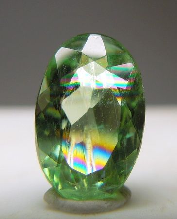 A rich green Hiddenite with good clarity with fine inclusions and an iris effect depending on the angle that the light hits it