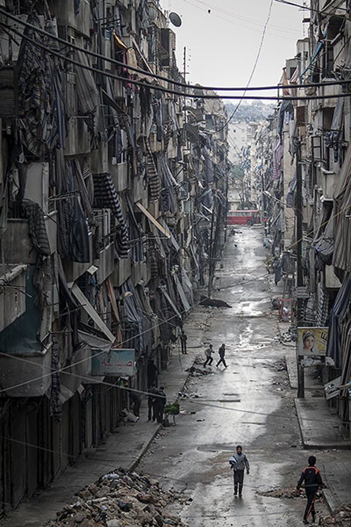 Syrians walk past damaged homes during heavy fighting in Aleppo // by Narciso Contreras