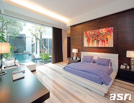 Paduan view kolam renang, gaya furnitur, dan material finishing menciptakan suasana alami dan modern pada kamar tidur utama yang diperindah oleh lukisan etnik koleksi pemilik rumah.