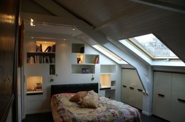 Aménagement d'une suite parentale sous combles à Paris: création d'une tête de lit à la fois graphique et pratique, rangements.