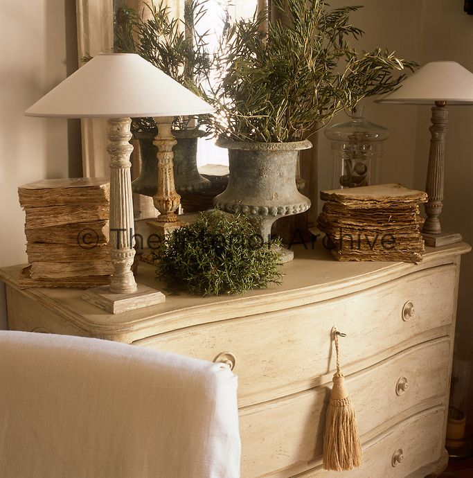 Avignon - Two table lamps with white shades, a dried foliage arranged in a stone urn and a mirror are arranged on a neutral chest of drawers.