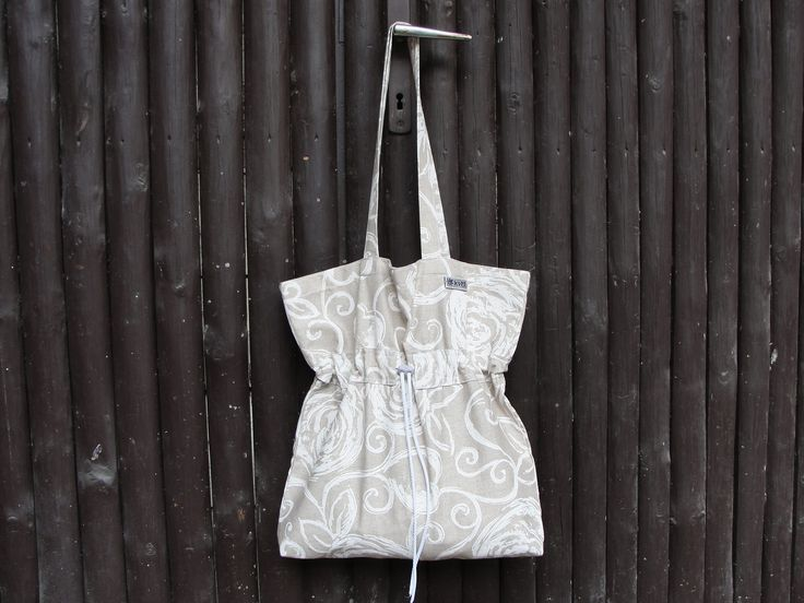 Moderní stylová taška přes rameno nebo do ruky vhodná na výlety pro nákupy nebo k vodě. Velmi pevné bavlněné plátno v béžovém tónu s ornamenty. Ve dvou třetinách tunýlek na stažení kabelky. Ideální pro každodenní nošení.
