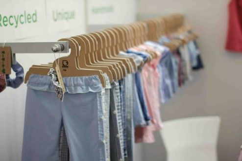 Cardboard hangers for a recyclable  display option. The store upcycles shirts into baby clothes.