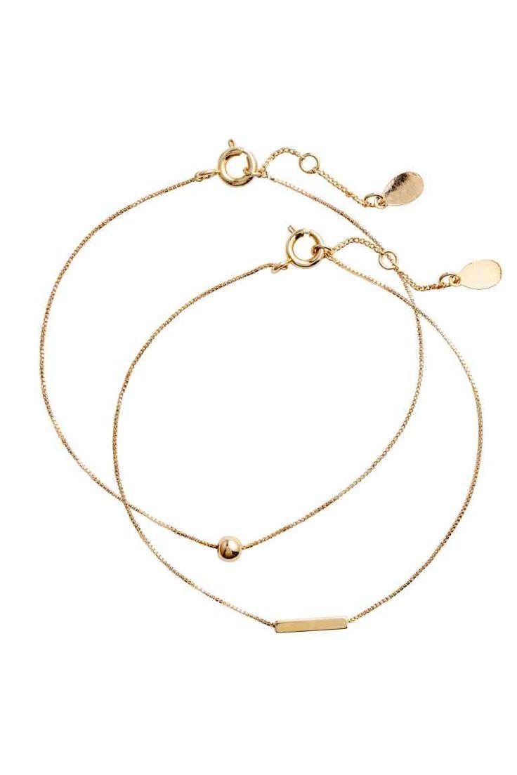 Bracciali placcati oro, 2 pz: PREMIUM QUALITY. Due bracciali formati da una catena sottile di metallo con ciondoli decorativi. Placcati in oro a 22 carati. Lunghezza regolabile.