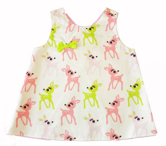A handmade reversible baby dress, designed by you!This picture shows the reverse.An ideal newborn or baby shower gift.Design your little baby dress just how you want it. You can add sleeves, a pocket or a bow.Choose your fabric combinations 1 patterned, 1 plain.Tell me the size y...