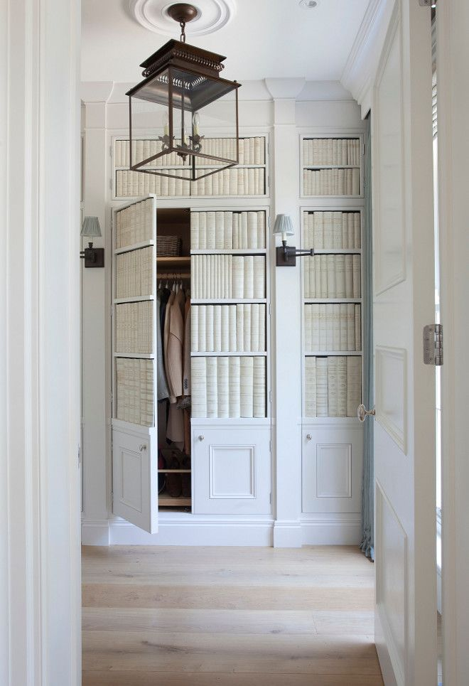 False library wall with ceramic book ends, leading to a closet.