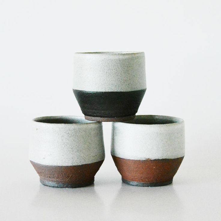 Three handthrown stoneware cups w. black slip and white glaze. The red color is the raw clay, which has a rough feel. Dishwasher safe. H: 8 cm.Ø: 8,50 cm.The price includes all three as they are sold as a set.