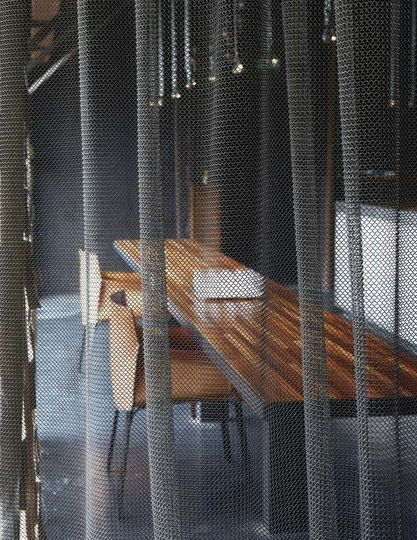 Derrière un rideau de métal, une longue table de salle à manger appelle à la convivialité. Plus de photos sur Côté Maison http://petitlien.fr/7bcd