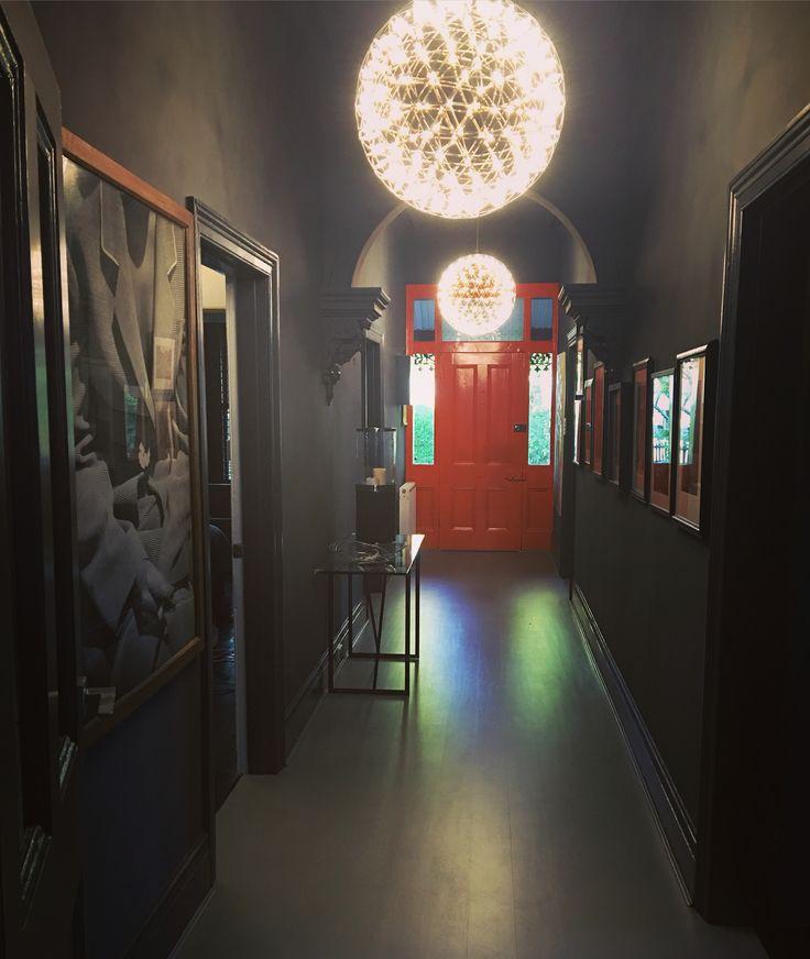 Hallway with dark coloured walls, grey floorboards, bright orange front door and mooi Raimond suspension lights