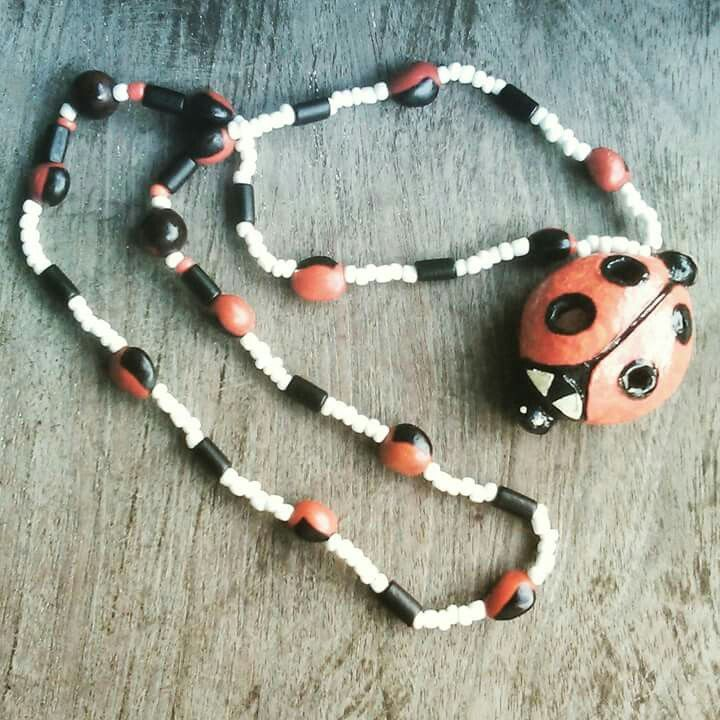 Ocarina collar en forma de mariquita hecho en arcilla. Facebook: Sonidos del Alma.