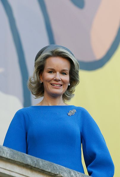 Queen Mathilde of Belgium poses for photos in front of a giant poster of comic character Tintin on October 5, 2016 in Paris, France.