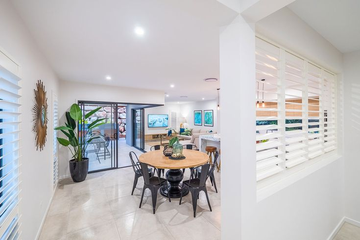 Dining room. White window louvres, shutters. Tropical plant.