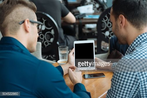 Casual men using digital tablet for communication and social networking : Stock-Foto
