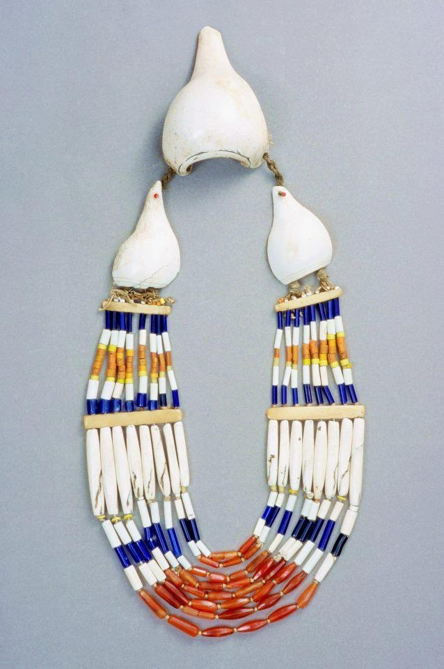 eavy Naga necklace, of a well known but desirable type, worn with the large shell hanging on the back as a counterweight to the remainder. Nagaland (India), Angami Naga people, mid 20th c. Cut conch shells, shell beads, glass and carnelian beads, bone spacers. From *Ethnic Jewellery and Adornment*, p. 337.