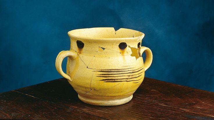 Cette tasse en céramique à deux anses de type « Staffordshire slipware » est dite « à posset ». Le posset, très prisé par les Britanniques, est fait de lait chaud mélangé à de la bière, du vin ou un autre alcool, auquel on ajoute du sucre et des épices. On le prend comme boisson et comme remontant. Elle a été découverte sur le site de la maison Guillaume-Estèbe, dans un contexte archéologique du XVIIIe siècle. Photo : Marc-André Grenier 1998 © Ministère de la Culture et des Communications