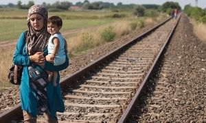 A woman who has just crossed the border from Serbia into Hungary carries her child along a railway line that links the two countries