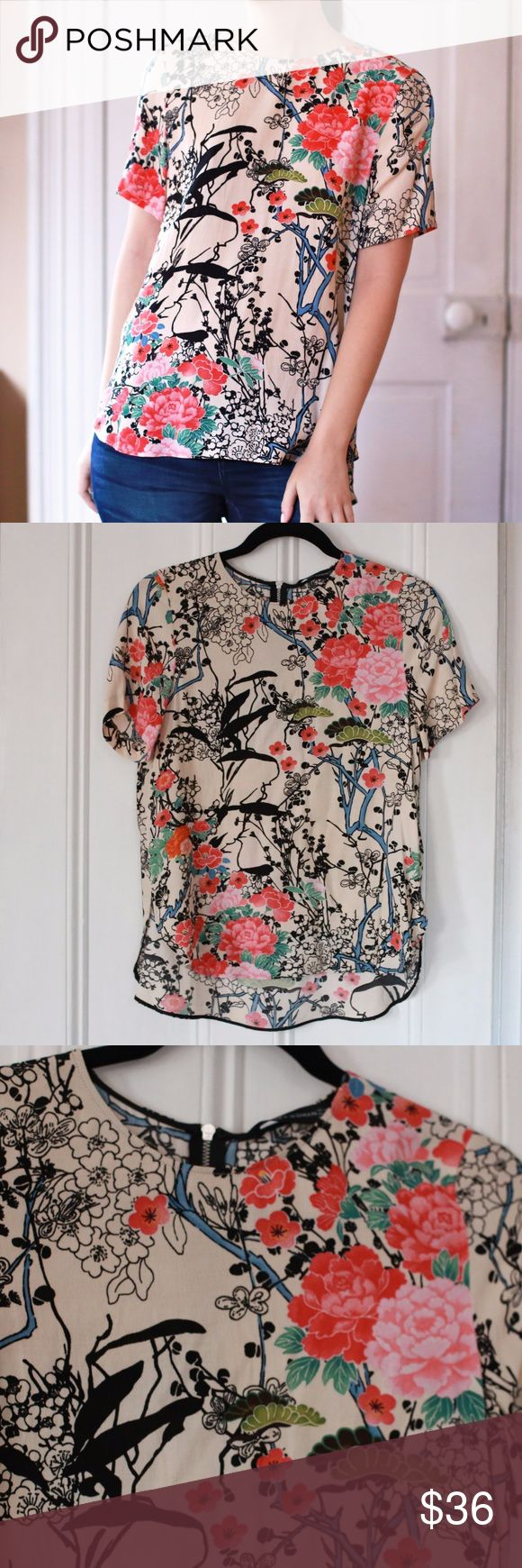 """Zara Floral Graphic Short Sleeve Blouse Top A lovely graphic floral print top from Zara Woman. The material is like a crepe and 100% viscose. I wore this only once (briefly for a photoshoot). The design has black and white flowers and some bigger pink ones over a cream base-- reminiscent of a Japanese floral print kimono. Zips up behind the neck. About 24"""" in length and 17"""" from armpit to armpit. Zara Tops Blouses"""