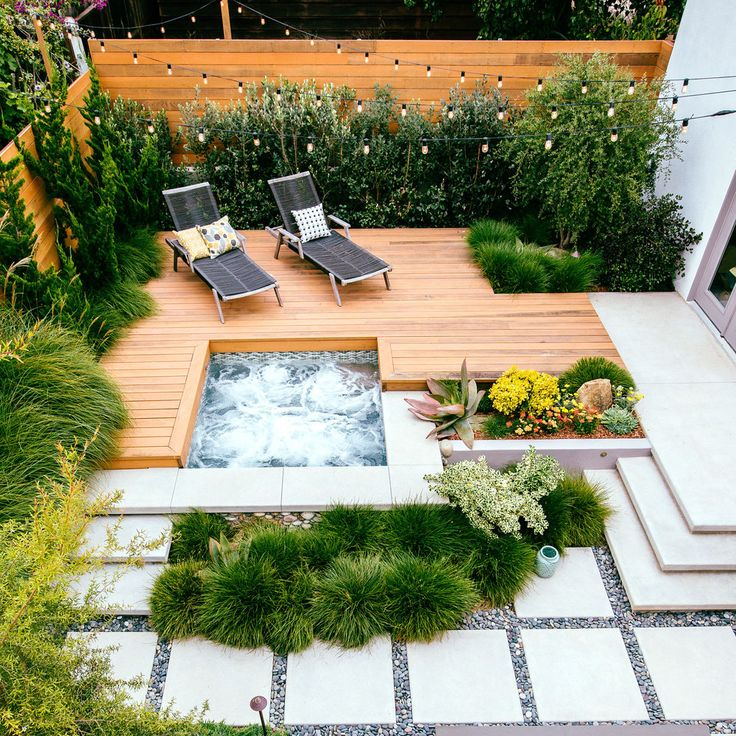 A rock wall fringed with Berkeley sedge separates a lower paved patio from a raised redwood deck and hot tub. The level change makes the small backyard appear larger.