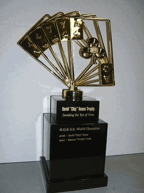 """The David """"Chip"""" Reese Trophy is a custom award created for the World Series of Poker. This award is a perpetual trophy that recognizes the H.O.R.S.E. World Champion each year. The award was named after the late David """"Chip"""" Reese, regarded by many to have been the greatest cash game player that ever lived. The award stands 21"""" tall, and incorporates Reese's winning hand in the inaugural event, along with a gold and diamond piece that is also used for the winner's bracelet."""