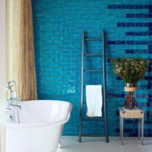 Salle de bain avec baignoire pattes de lion et au murs, des carreaux de céramique déclinant les bleu clair et le bleu doncé