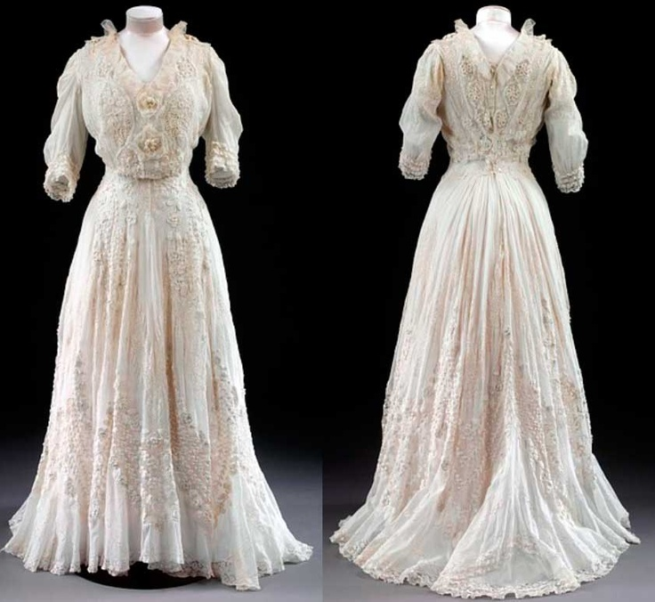 Summer dress for garden parties and fêtes. White cotton lawn, with handmade lace insertions and cotton crocheted flowers, 1904-1908. Possibly made in France. Although this dress looks soft and pliable, the wearer would have worn rigid corseting underneath.
