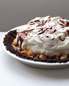 Chocolate appears three times in this black-bottom pie: The crust is made of chocolate wafers, the filling is rum-flavored ganache topped with macadamia nuts, and the whipped cream topping is swirled with more chocolate.