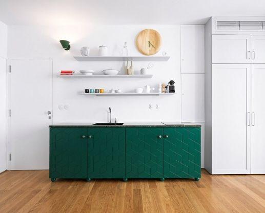 Kuchyň je koncipovaná tak, aby dokonale zapadla do uvolněného stylu obývacích prostor. Zelené kuchyňské skříňky a bílé otevřené police působí spíš jako úložný nábytek obývacího pokoje