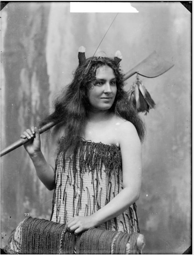 Studio portrait of an unidentified young woman. She is wearing traditional Maori clothing and is wearing a hui tail feather behind each ear. Photographed standing beside a chair from waist up. She is holding a tewhatewha in her right hand and resting it on her shoulder. Photograph taken by William Henry Thomas Partington in early 1900s.