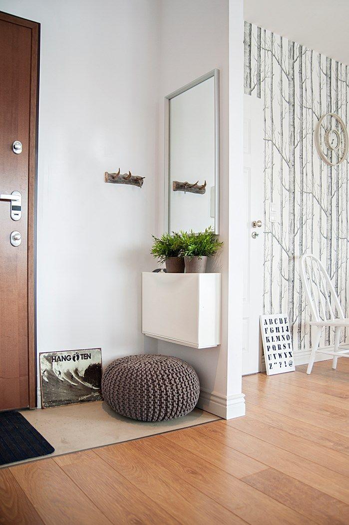 Hall de entrada com espelho e vasinhos de planta.