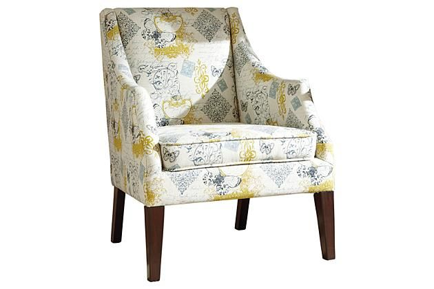 Accent chair with brown wooden legs with a yellow, blue, and white patterned fabric