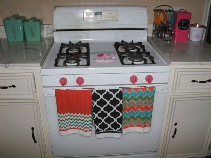 pink painted oven knobs. eclectic. dollar store dish towels and hello kitty spoon rest.