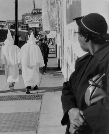 "A woman watches as robed Ku Klux Klansmen walk in downtown Montgomery, Alabama prior to a cross burning rally that night, November 24, 1956. Circulars advertising Klan meeting said, ""We believe in white supremacy, we need you -- you need us."" Negroes have boycotted city buses for nearly a year in protest against segregation.  Photo credit: Associated Press"