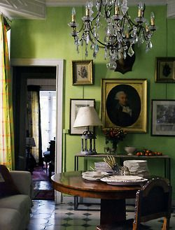 Wall gallery of eclectic paintings paired with a modern lime green wall ... love the pairing of old  new design elements.