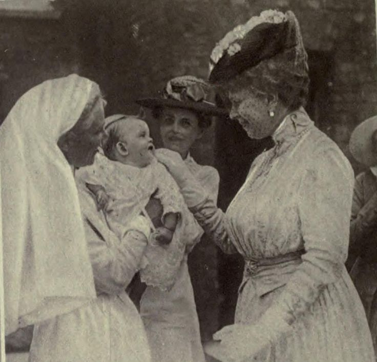"Another rare"" image of Queen Mary smiling , this time at a baby, during wartime.1917"