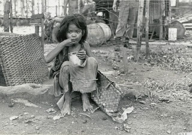 Indonesian child eating food offered by Dutch soldiers, 1947.