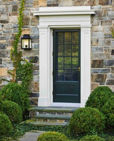 Wall of different sized rocks, great door frame, black door with glass panels, boxwood bushes and climbing ivy