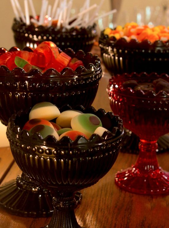 Iittala Marimekko Bowl selections in black and plum and red used as candy bowls filled with gummy eyeballs, worms, spiders, and candy corn