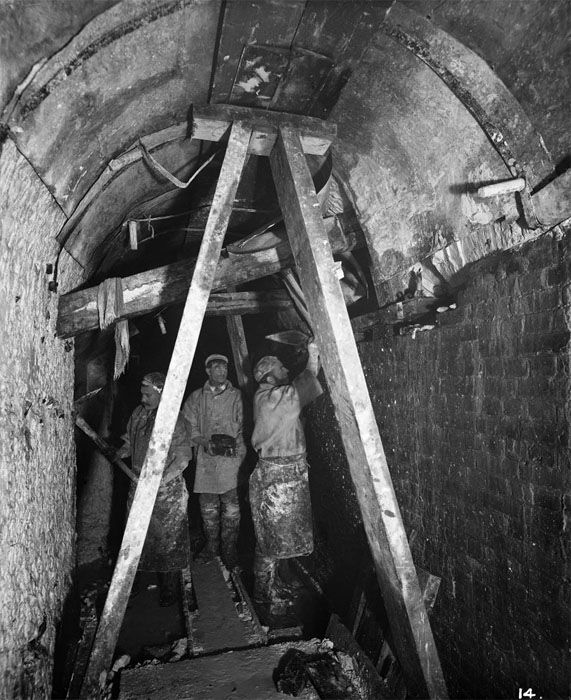 Men working in a chamber or tunnel at the East London Water Works, Barking. The subject of this photograph is recorded as 'bricking up' in the daybook of Bedford Lemere, the company who took this series of photographs. The workmen appear to be adding a layer of bricks inside the tunnel that has been cut in the rock. This would have made it safer and helped to make it more waterproof. The workmen are dressed for working in very wet conditions.