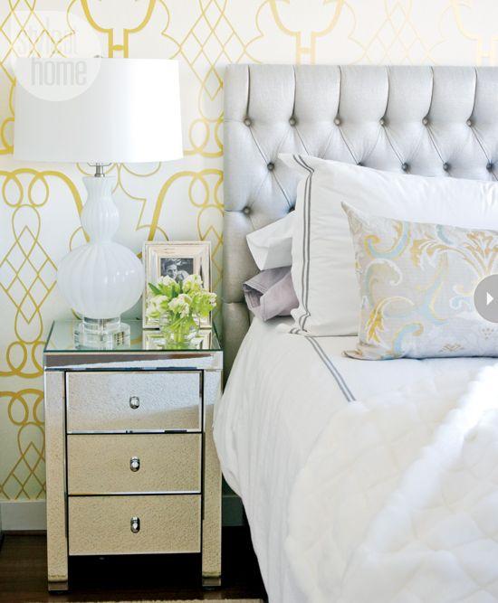 Papel de parede branco com dourado, criados-mudos espelhados, luminária de mesa de vidro branco e peles artificiais jogadas na cama dão a este belo quarto um ar sofisticado.