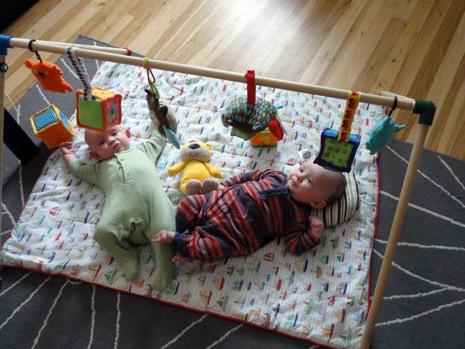 DIY baby gym made with wooden dowels.