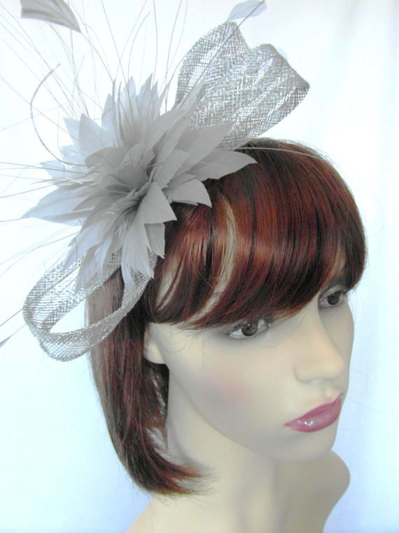 Susan is a metallic silver sinamay fascinator in a looped bow shape. It is decorated with a grey feather flower, coque feathers and peacock hurl feathers It sits on a very fine silver coloured metal hairband It is approximately 9 inches long and 3-4 inches wide Good neutral colour which goes with most other colours
