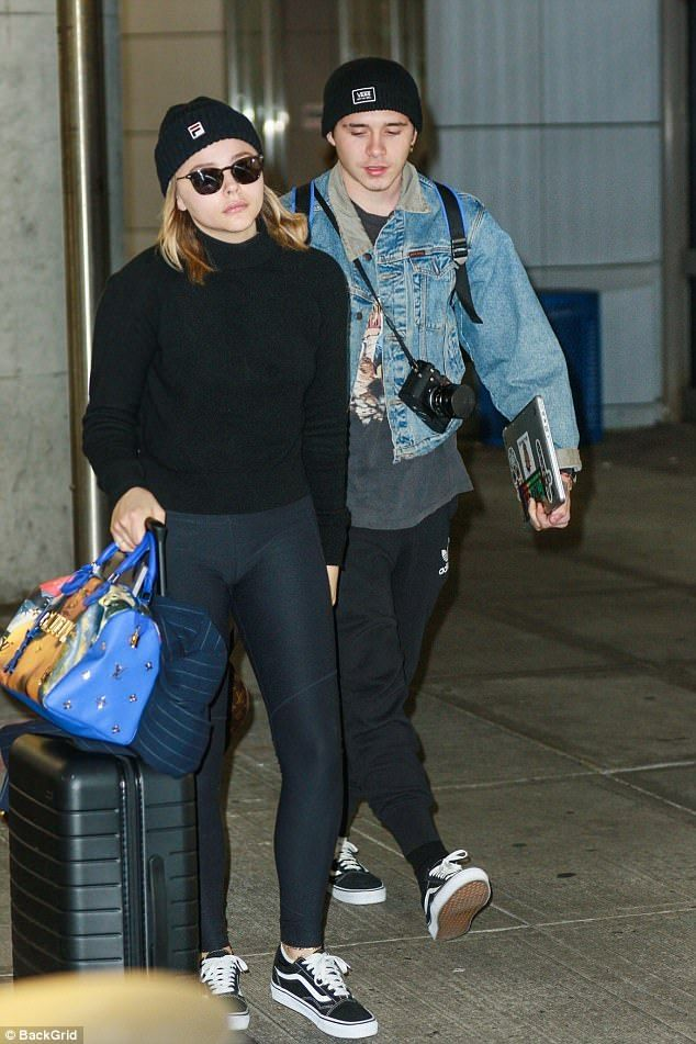 Glum Chloe Moretz seeks solace in the arms of boyfriend David Beckham as they jet into New...