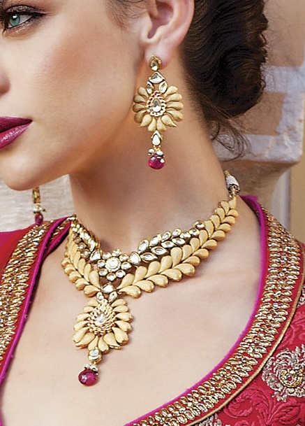 Necklace and earrings in gold polish with kundan and ruby pink stone. Priced at $439.
