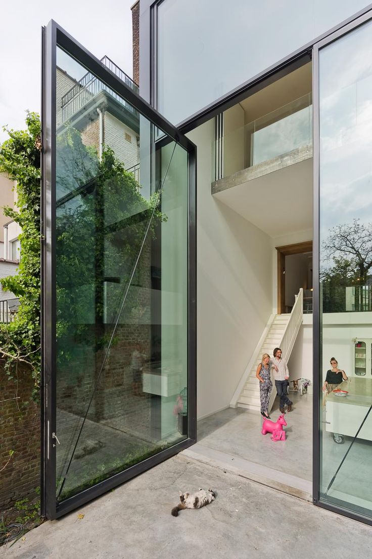 These sleek and contemporary gigantic custom-made glass pivoting doors measure in at 9 ft (3m) wide by 52 ft (6m) high and they weigh 4400 lbs (2000 kg) each, and yet may effortlessly be pushed open with just one finger! #PivotingDoor #PivotingGlassDoor #GlassDoors